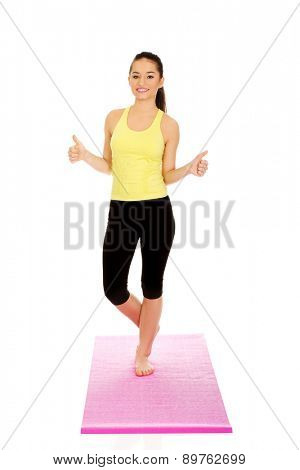 Attractive fitness woman showing thumbs up.