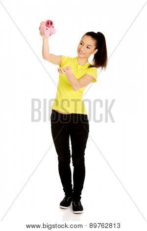 Happy teenage woman shaking piggybank.