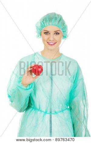 Female surgeon doctor holding heart model.