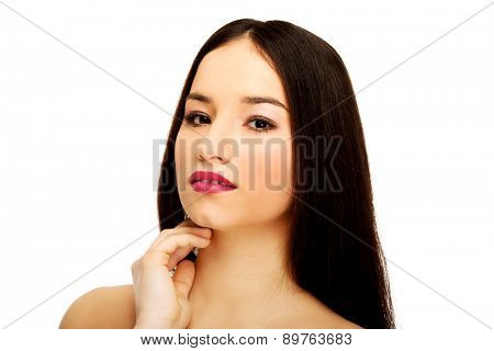 Beautiful woman with full make up touching neck.
