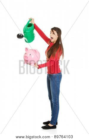 Young woman waters piggybank with watering can.