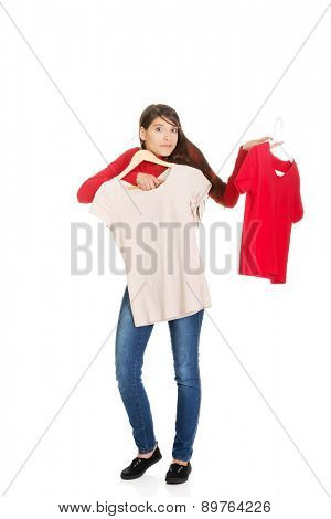 Confident young woman choosing shirt.
