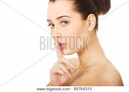 Beautiful glamour woman making hush gesture.