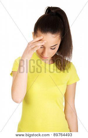 Teen woman with a headache holding head.