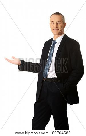 Smiling businessman holding something on his palm.