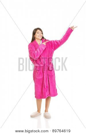 Beautiful woman wearing pink bathrobe pointing aside..