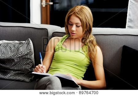 Young teenage woman learning to exam on a sofa.