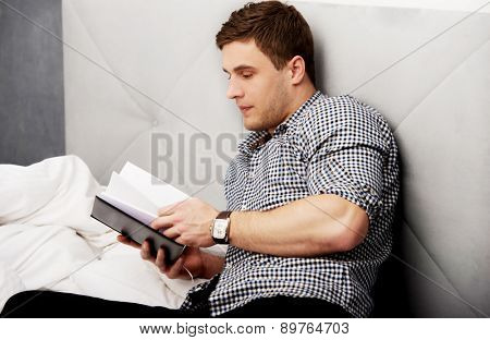 Handsome thoughtful man reading a note in his bed.