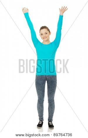 Teen woman with hands up holding copy space.