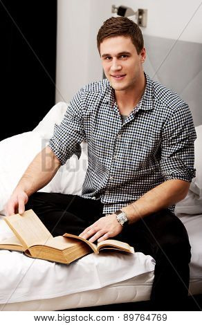 Handsome man with a book in his bed.