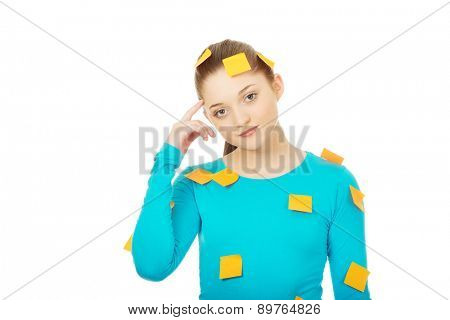 Beautiful young woman covered with post it notes.