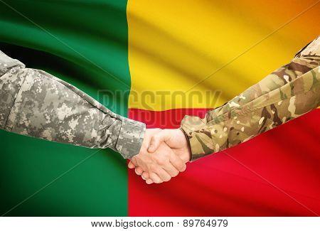 Men In Uniform Shaking Hands With Flag On Background - Benin