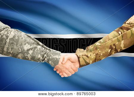 Men In Uniform Shaking Hands With Flag On Background - Botswana