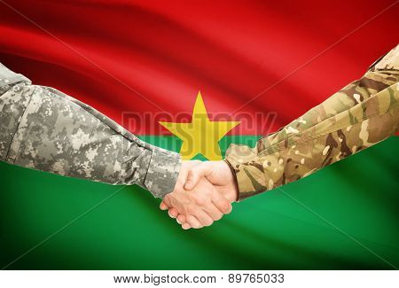 Men In Uniform Shaking Hands With Flag On Background - Burkina Faso
