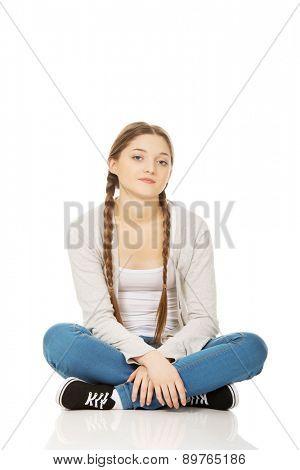 Beautiful teen woman sitting cross legged.
