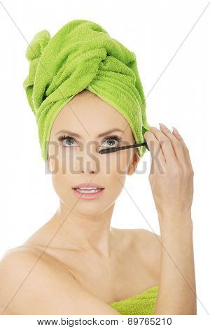 Woman with towel turban applying mascara.