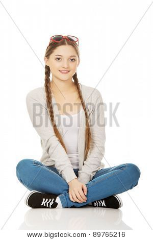 Funny teen woman sitting wearing sunglasses.