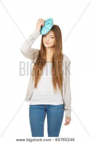 Teen woman with headache and ice bag.