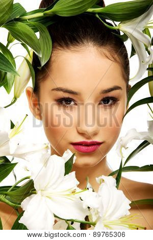 Beauty face of young woman with lily flowers.
