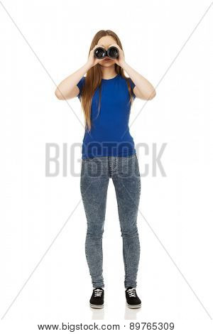 Beautiful teenage woman with binoculars.
