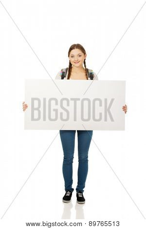 Happy teenage woman with blank billboard.