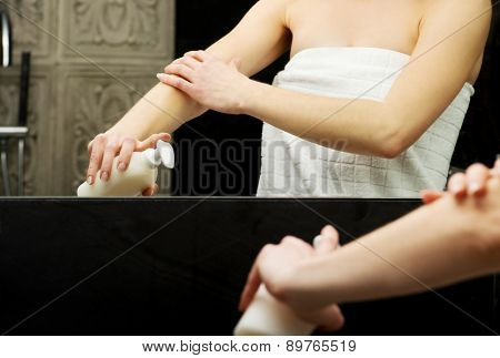 Beautiful woman with body lotion in bathroom.