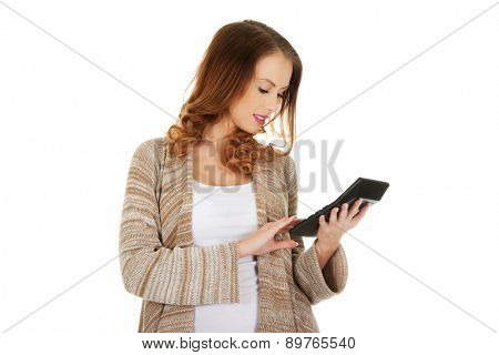 Beautiful casual woman with calculator.
