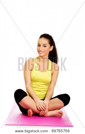 Fitness woman sitting cross legged on exercise mat.