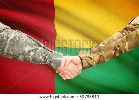 Men In Uniform Shaking Hands With Flag On Background - Guinea-bissau