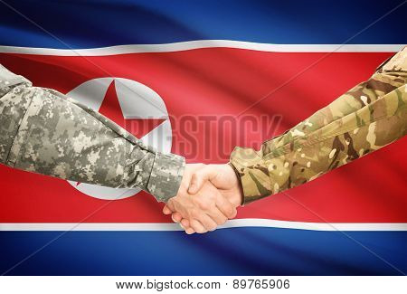Men In Uniform Shaking Hands With Flag On Background - North Korea