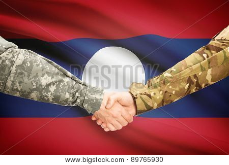 Men In Uniform Shaking Hands With Flag On Background - Laos