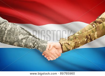 Men In Uniform Shaking Hands With Flag On Background - Luxembourg