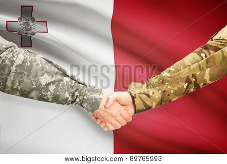 Men In Uniform Shaking Hands With Flag On Background - Malta