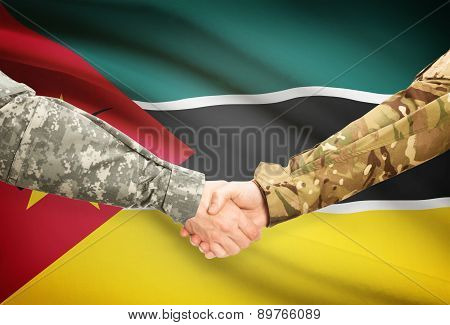 Men In Uniform Shaking Hands With Flag On Background - Mozambique