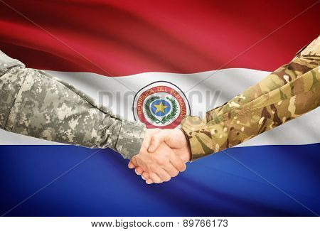 Men In Uniform Shaking Hands With Flag On Background - Paraguay