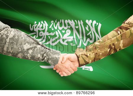 Men In Uniform Shaking Hands With Flag On Background - Saudi Arabia