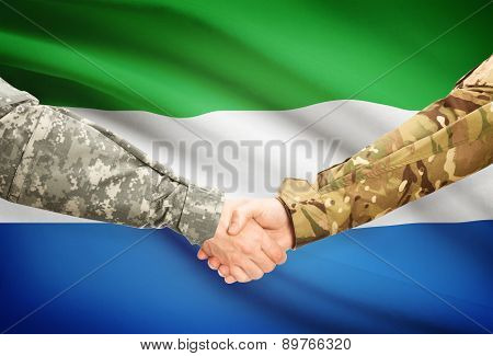 Men In Uniform Shaking Hands With Flag On Background - Sierra Leone