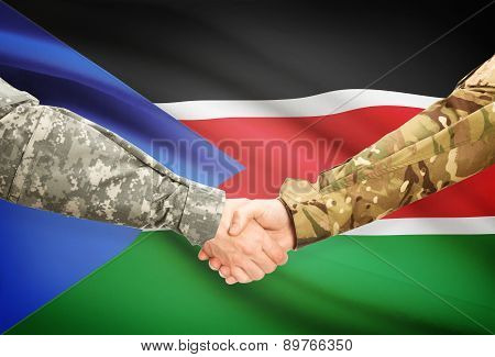 Men In Uniform Shaking Hands With Flag On Background - South Sudan