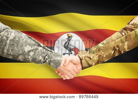 Men In Uniform Shaking Hands With Flag On Background - Uganda