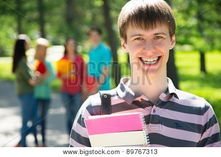 Happy student outdoors with his friends