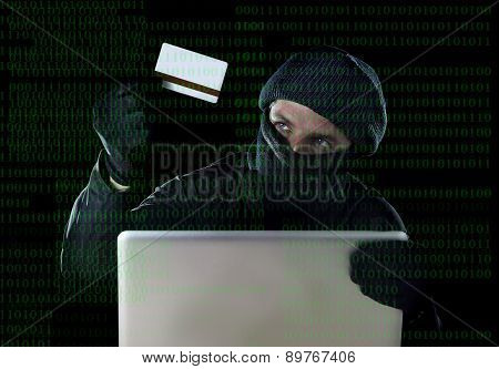 Man In Black Holding Credit Card Using Computer Laptop For Criminal Activity Hacking Password And Pr