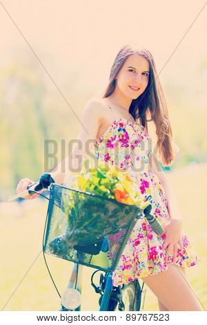 Young woman in short colorful dress with long hair rides a bicycle with basket and flowers tour summer city park, look and smile to camera. Altered toned photo