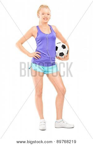 Full length portrait of a blond female athlete holding a football and listening music on headphones isolated on white background