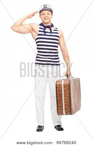 Full length portrait of a young male sailor saluting towards the camera and holding a briefcase isolated on white background