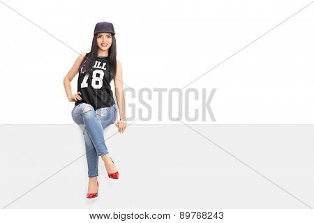 Young woman in a hip hop outfit sitting on a blank billboard and looking at the camera isolated on white background