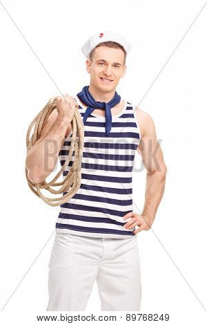 Vertical shot of a young sailor in a striped shirt holding a rope around his shoulder isolated on white background