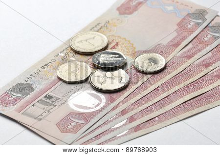 One hundred Dirham currency notes and coins on white background.