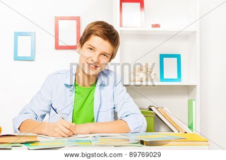 Smart boy with books and textbooks on the table