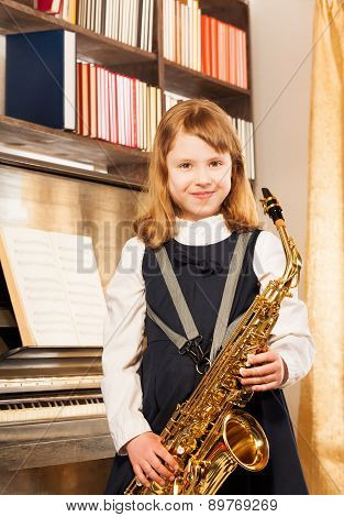 Beautiful girl holding alto saxophone indoors