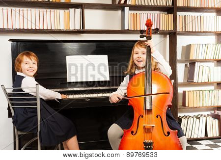 Girls in dresses playing on cello and the piano